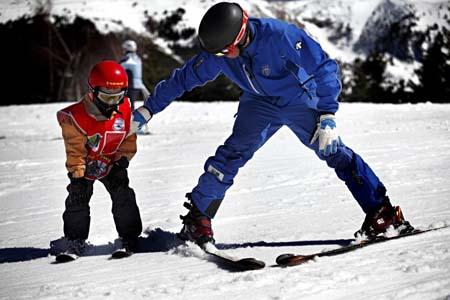 Обучение горным лыжам ребенка с инструктором.